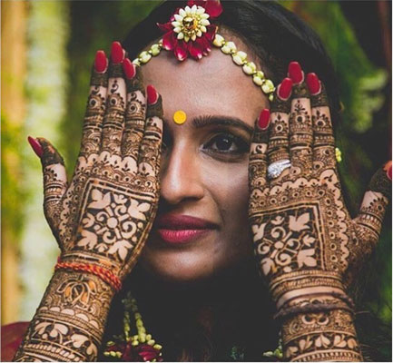 Aniket Mazumdar | Indian bride with super pretty gap style mehendi | bridal mehendi ideas to book mark | Indian bride wearing a pretty floral mathapatti