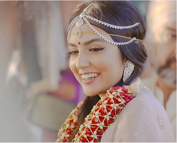 pretty bride wearing a diamond mathapatti with a stunning red and white jaimala   photo by colorblind productions