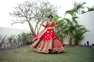 Nindiya and Nirmal | Indian bridal lehenga | Real flower lehenga | The bride twirling in her red and gold bridal lehenga with seven vows embroidered on it.