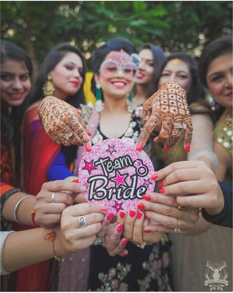 Squad accessories for Indian Weddings | Team bride metallic Badge that you can use | Ideas for the bride's side bridesmaids | team bride Badges | Bridesmaid's Gift ideas | Bride posing with her BFFs with a pink team bride badge and bride sunglasses