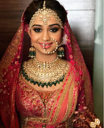 stunning indian bride wearing a pretty red and gold lehenga along with a pretty gold and emerald Kundan set | Mathapatti with a dainty jail