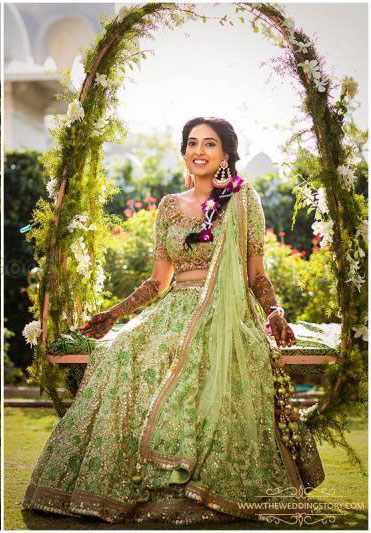 Teej party ideas | Teej Celebrations | Indian bride in light green lehenga with floral braid on a green swing | pc- story weavers