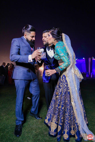Netika and Kushank | Destination wedding in Jaipur | The bride in a navy blue lehenga and the groom in a tuxedo having a fun and candid moment with their friend.