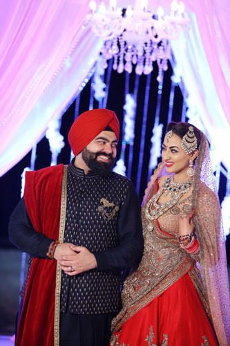 Bavleen and Kushal   Destination wedding in Goa   The bride in he beautiful wedding lehenga smiles at her groom in black wedding outfit.