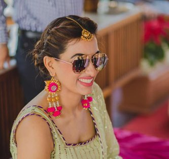 Bavleen and Kushal | Destination wedding in Goa | The bride smiles in her mehendi outfit of sea green coor with her shades on.