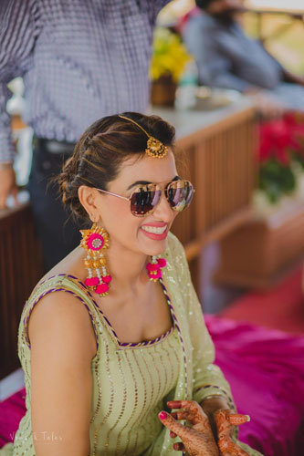 Bavleen and Kushal   Destination wedding in Goa   The bride smiles in her mehendi outfit of sea green coor with her shades on.