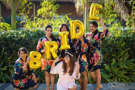 Joshua and Shona | Christian wedding | DIY ideas | The bride tribe wearing matching robes and posing with cute foil baloons while the bride smiles in a white robe and tiara.