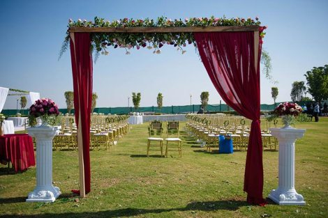 Joshua and Shona | Christian wedding | DIY ideas | The marsala curtains with white flower decor on the entry gate looks so great.