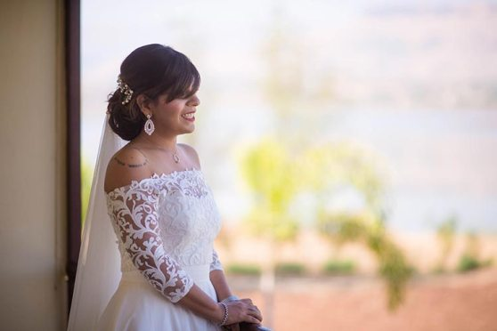 Joshua and Shona   Christian wedding   DIY ideas   The bride smiles in her white offshoulder gown.