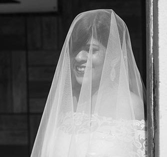 Joshua and Shona | Christian wedding | DIY ideas | The bride smiling behind her net sleeves.