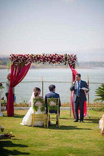 Joshua and Shona | Christian wedding | DIY ideas | The bride and the groom sitting on golden chairs with the Mr and Mrs tag on it.