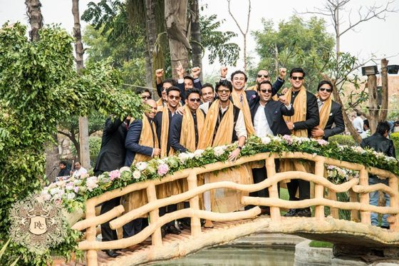 Nayana and Jai | Amazing Delhi wedding | Proposal story | Proposal ideas | The gang of boys in a acolor coordinated black and cream outfit posing on the wooden bridge.