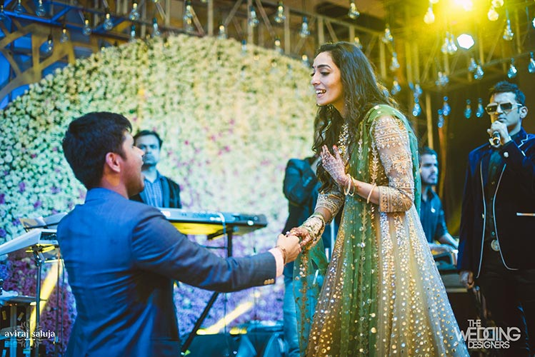 Jaya and Anish | Roka ceremony | Flower decor | The groom proposing the bride on one knee.