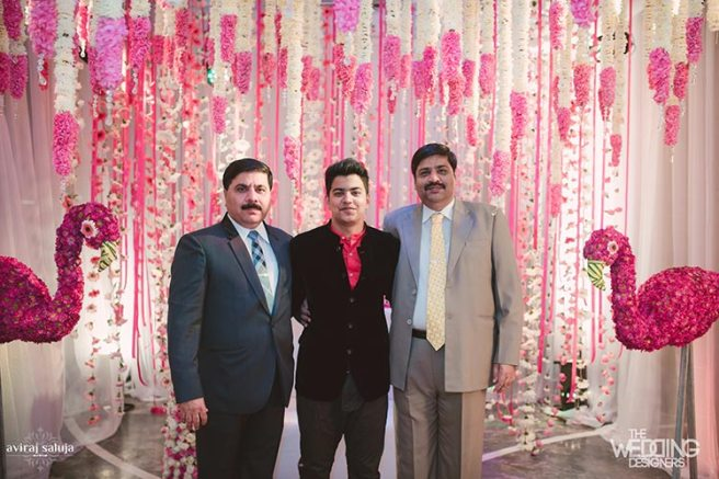 Jaya and Anish | Roka ceremony | Flower decor | The family posing at the flowered photo booth.