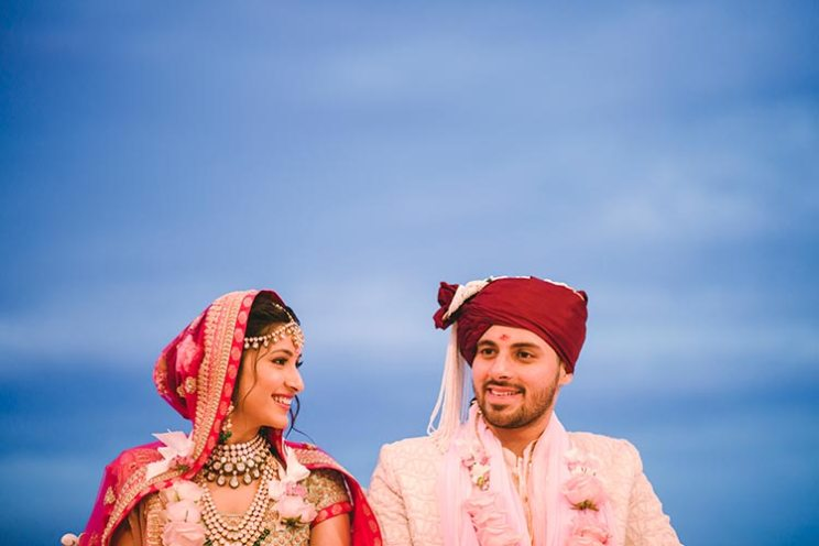 Sagar and Subiya | Destination wedding in Bali | The bride in a red lehenga and the groom in a beige sherwani smiling after the wedding rituals.