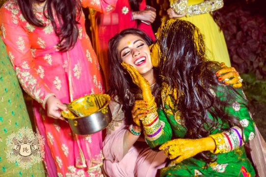 Nayana and Jai | Amazing Delhi wedding | Proposal story | Proposal ideas | The bride covered in haldi giving a peck to her sister.