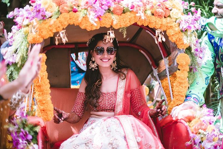 Sagar and Subiya   Destination wedding in Bali   The bride sitting on a flower laden rickshaw with her shades on.