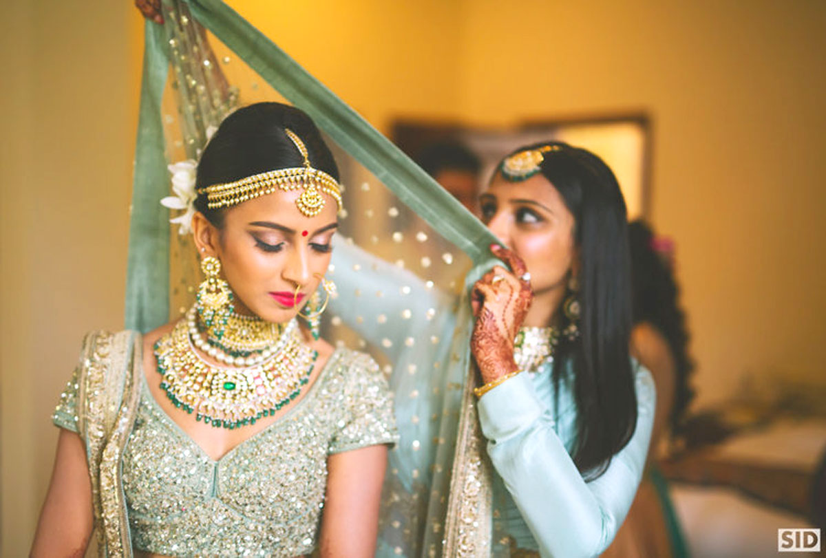 indian bride getting ready   bride in a pretty pale pastel green and gold blouse wearing a Kundan and emerald bridal set   bridesmaid draping the dupatta on the bride   total Sid photography