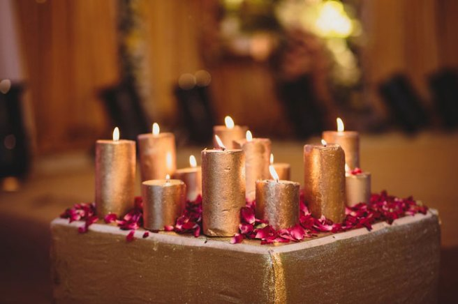 Nimisha and Hemant | Temple wedding in Delhi | The golden candles amidst the rose petals is an amzing wedding decor.