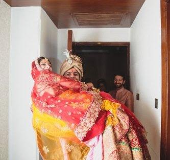 Nimisha and Hemant | Temple wedding in Delhi | The groom picks his bride in her wedding lehenga.