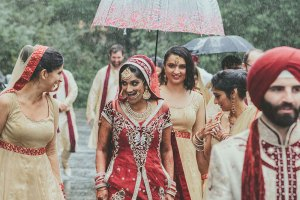 rain on your wedding day | bride with her bridesmaids under an umbrella