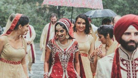 rain on your wedding day | bride with her bridesmaids under an umbrella
