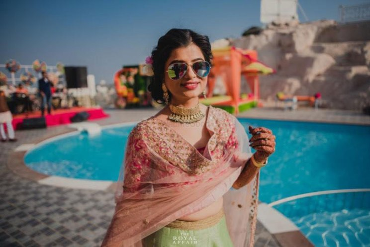 The v style dupatta drape. | bride in a green lehenga with a peach and gold dupatta rocking sunglasses at a poolside Mehndi | the royal affair photography
