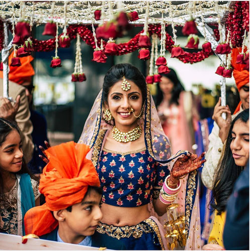 new phoolon ki chadar ideas for a perfect bridal entry | bride in a blue lehenga walking under a white phoolon ki chadar lehenga with rose tassels