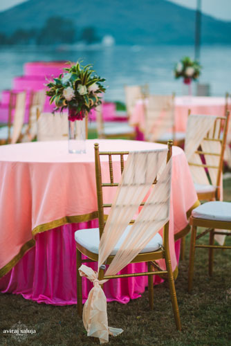 Pretty wedding table setting | pick underlays with light pink overlay and chivari chairs with cross bow chair backs for a beach wedding