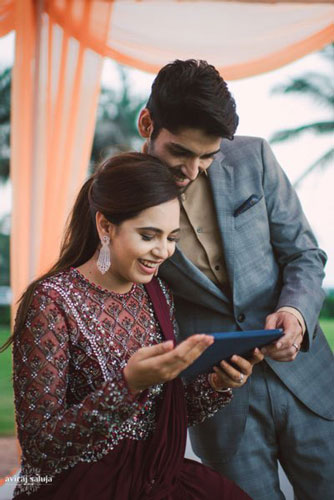 Ayushi and smaran wedding | couple looking at the iPad | reached to plan your beach wedding