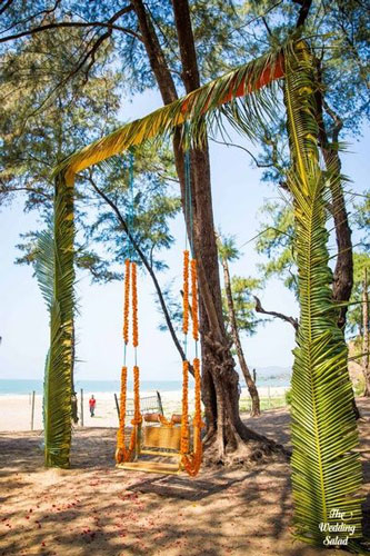 swing made for a beach wedding using local palm tree leaves | planning a beach wedding