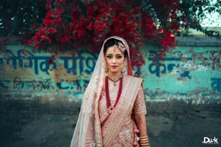 Indian bride wearing a pastel pink lehengas with a Kundan and ruby string wedding jewellery set