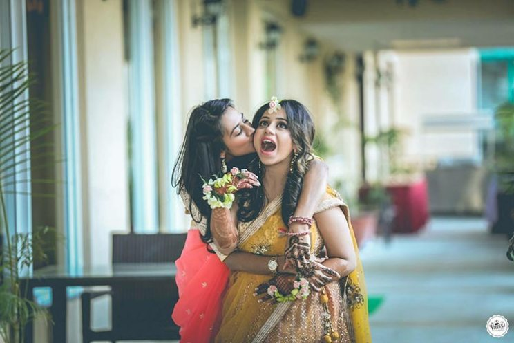 bride and her BFF together at their wedding | Indian bride in a yellow lehenga with floral jewellery