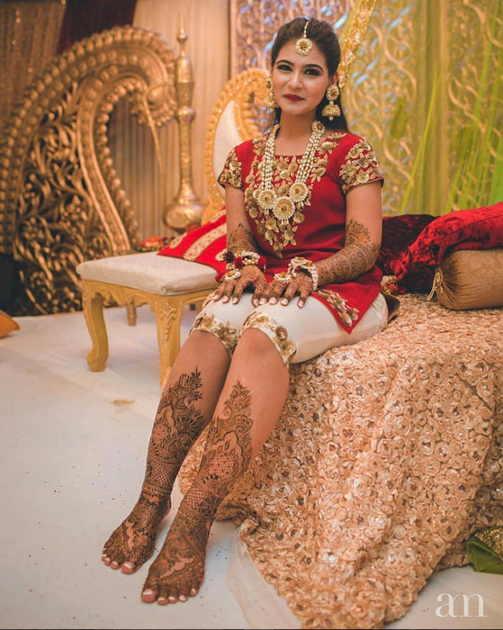 Indian bride wearing red blouse and shorts at her mehendi