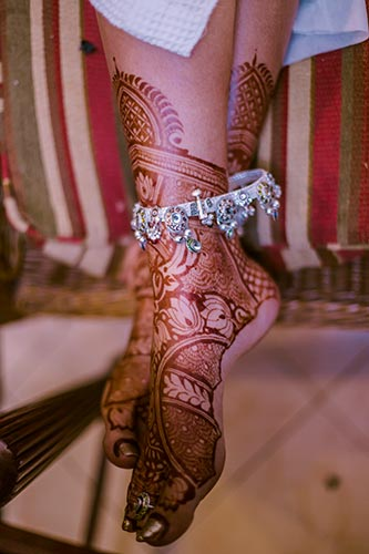 silver paayal on n Indian bride with henna feet