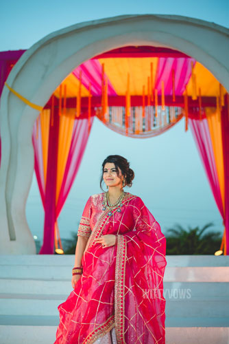 bride in a red traditional blouse and Kundan jewellery and white lehenga