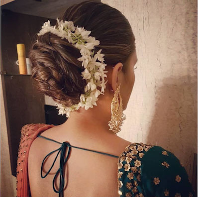 a curled layered bun with a Mogral gajra