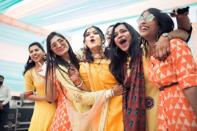 bridesmaids dancing together | bride enjoying her haldi ceremony |A beautiful love story of Stuti and Mukul, the high school sweethearts.