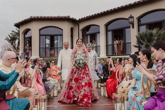 bride riya carrying white flowers walking down to the mandap | a stunning wedding in california