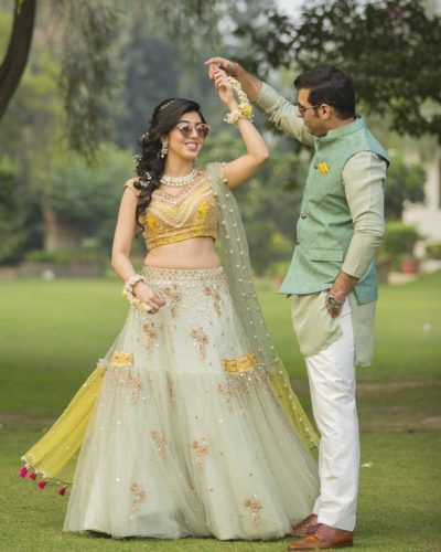 indian bride and groom in matching blue and yellow outfits for mehendi | twinning lehenga and was it coat and pocket square