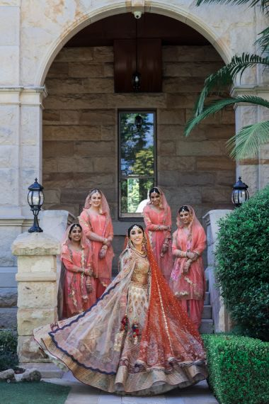 indian bride posing with bridesmaids in matching orange outfits   Cutest Surprise Proposal Ideas