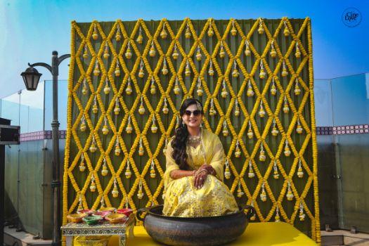 bride at her haldi ceremony | backdrop decor ideas