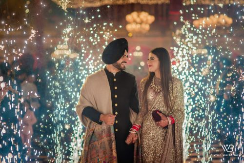 indian couple entry between the fire crackers | Sabyasachi Saree in Gold Sequins