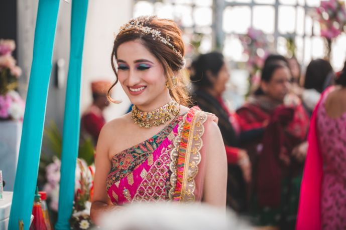 candid photo of bride to be on mehendi ceremony | Printed Lehenga  & a Gorgeous Off Shoulder Blouse - Megnha & Devansh