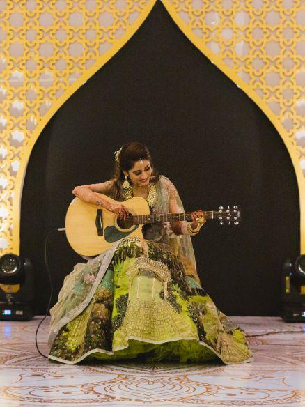 indian bride playing  guitar on sangeet night | Printed Lehenga  & a Gorgeous Off Shoulder Blouse - Megnha & Devansh