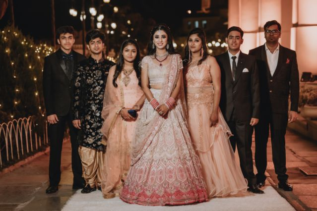 indian bride posing with her brothers and sisters | Destination Wedding in Udaipur
