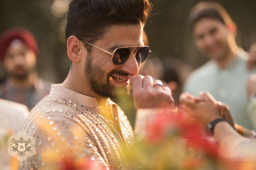 groom in sunglasses at mehendi ceremony | Mirror Work Lehenga for Mehendi