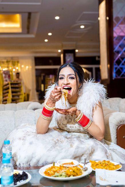 indian bride enjoying some food | Stunning Reception Look