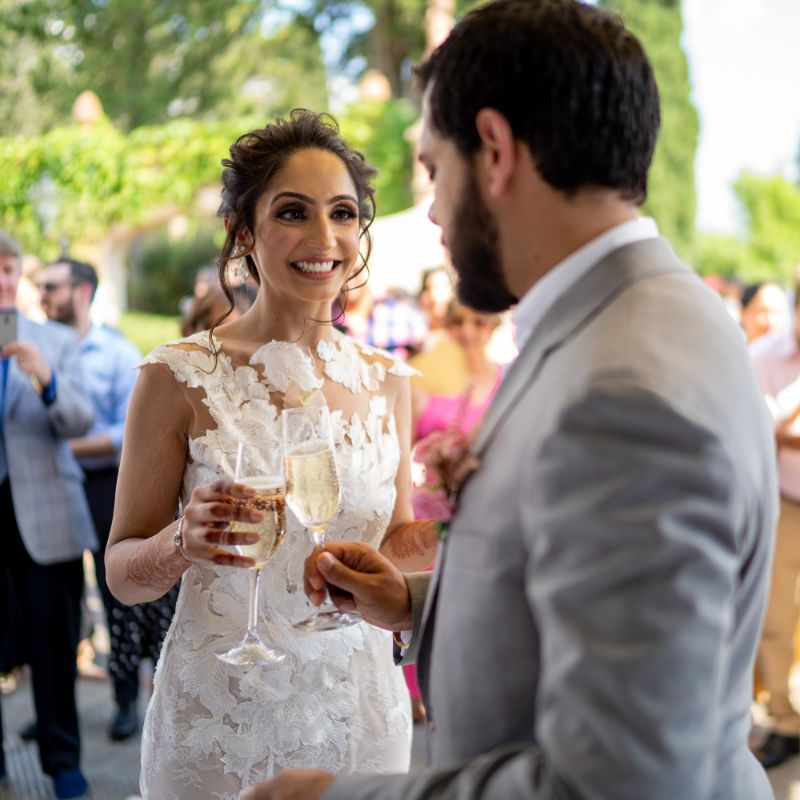 cheers to marriage | forma; bridal gown at nri indina wedding | white bridal gown | tuscany wedding indian couple dancing