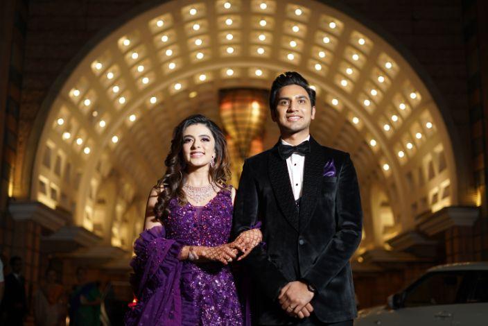 bride in baeutiful purple shimmer lehenga   groom in black tuxedo